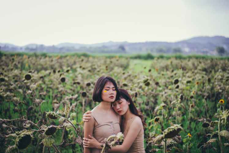 two women hugging on sunflower field