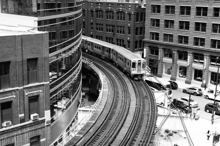 grayscale photography of train on railroad near buildings