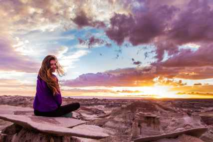 woman sits on mountain under cloudy sky at sunset